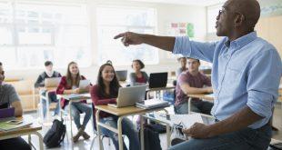 High school teacher calling on student in classroom
